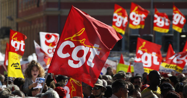 Private and public sector workers hold CGT union flags as they attend a demonstration over pension reforms in Nice, southeastern France October 12, 2010. French trade unions began a fresh wave of strikes against pension reform on Tuesday, testing the resolve of French government as the unpopular bill edges closer to becoming law. Rail services, flights and sea ports ran below capacity as the unions kept up their battle against a plan to make people work longer for their pensions, including raising the minimum retirement age to 62 from 60.   REUTERS/Eric Gaillard    (FRANCE - Tags: POLITICS EMPLOYMENT BUSINESS CIVIL UNREST)