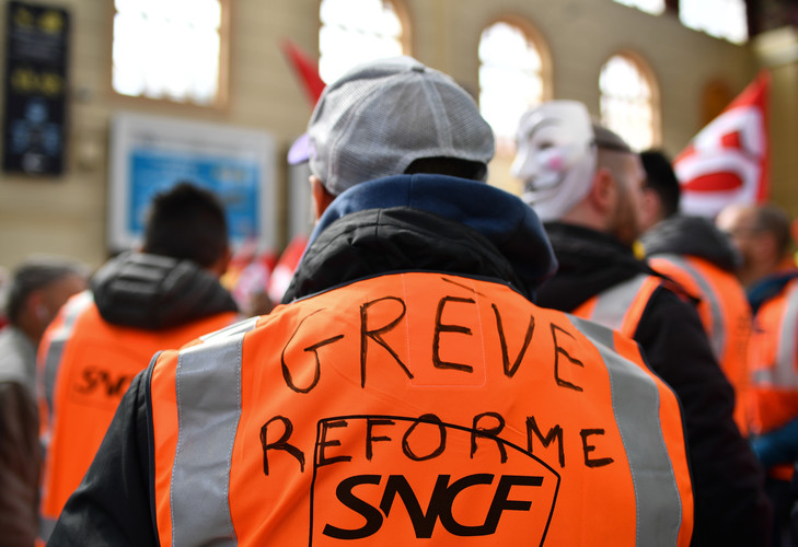 A rail worker wearing a SNCF high visibility vest with the words, 'reform strike' , takes part in a rally called by the French trade union the General Confederation of Labour (CGT) at the Saint-Charles train station in the southern coastal city of Marseille on April 4, 2018, on the second day of three months of rolling rail strikes. - Staff at French state rail operator SNCF walked off the job from 7.00 pm (1700 GMT) on April 2, the first in a series of walkouts affecting everything from energy to garbage collection. The rolling rail strikes, set to last until June 28, are being seen as the biggest challenge yet to the President's sweeping plans to shake up France and make it more competitive. (Photo by BERTRAND LANGLOIS / AFP)